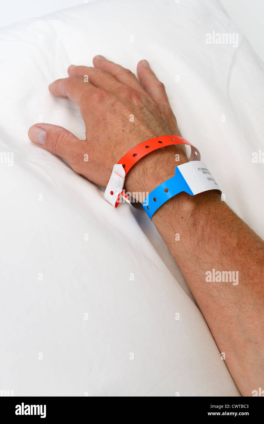 Hand and arm of a man in hospital with identification wrist bands - Stock Image