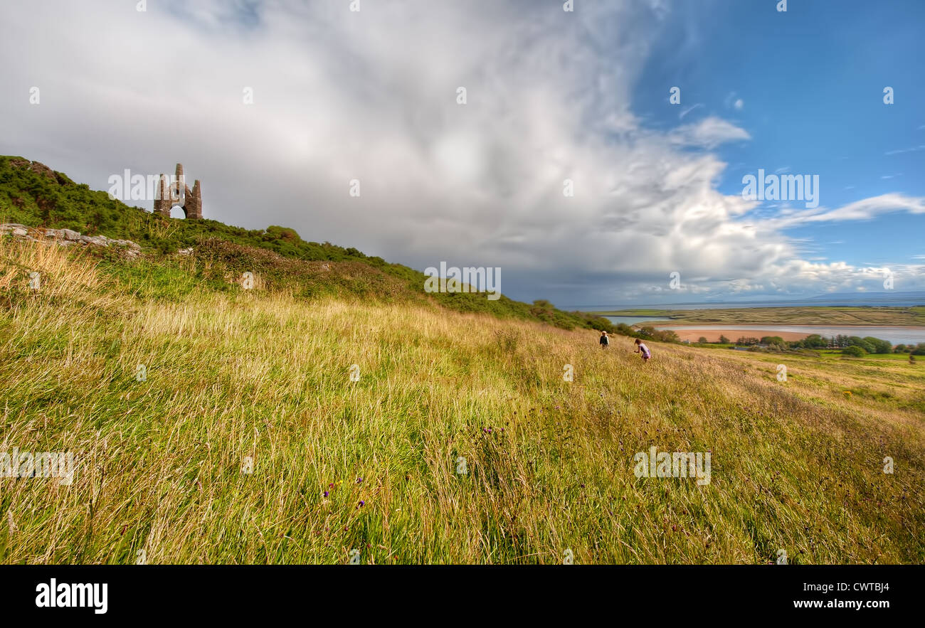 Children climb towards a Victorian Folly standing on a hill overlooking Lacken Strand in County Mayo, Ireland during - Stock Image