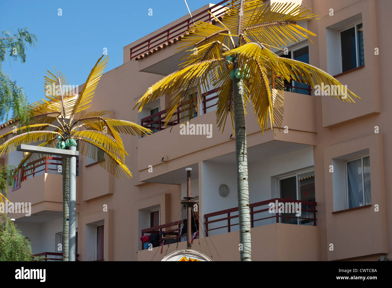Plastic palm trees outside a tourist apartment block in Ibiza island, Spain. - Stock Image