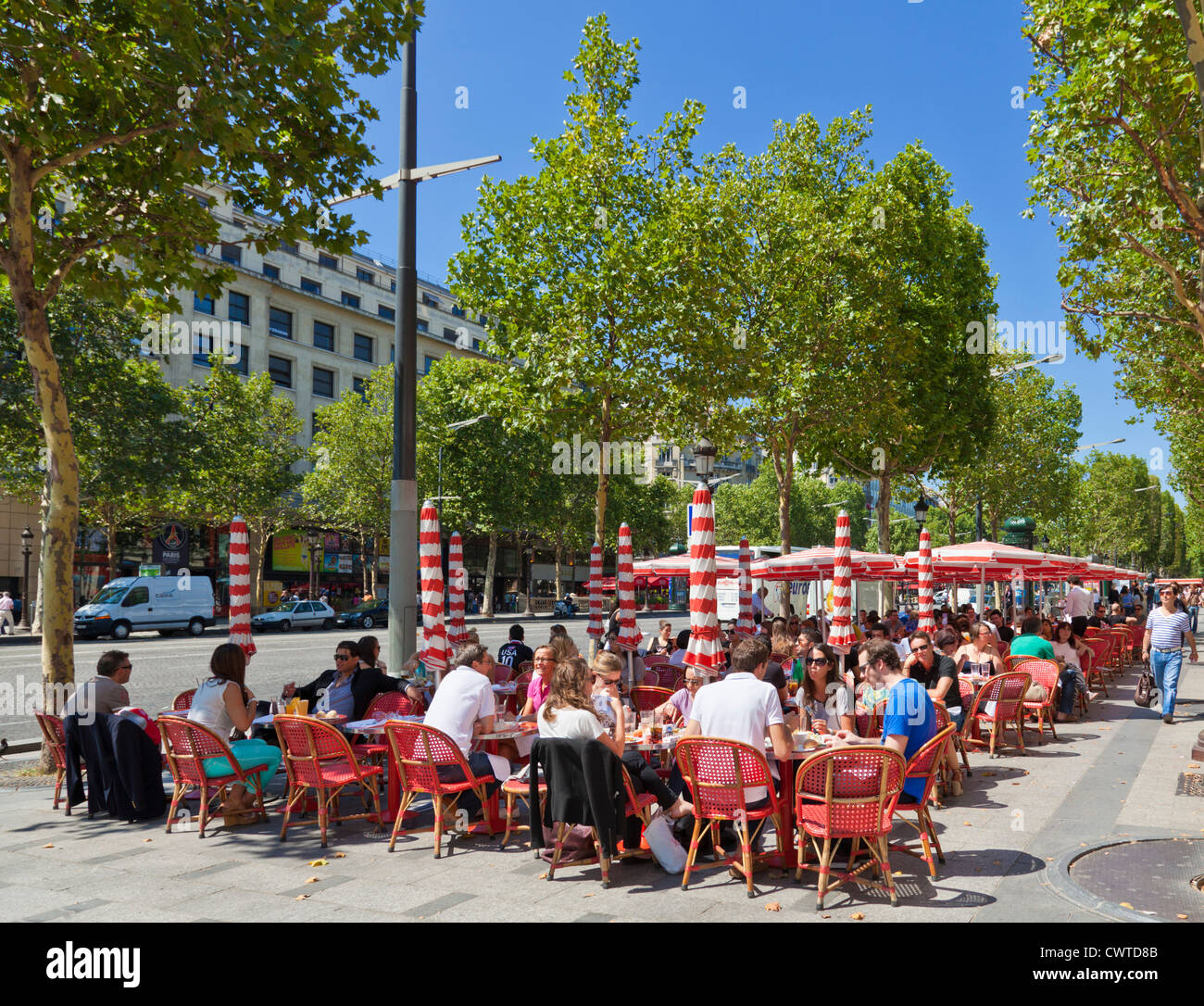 People sitting at a pavement cafe on the famous street the Champs Elysees avenue Paris France EU Europe - Stock Image