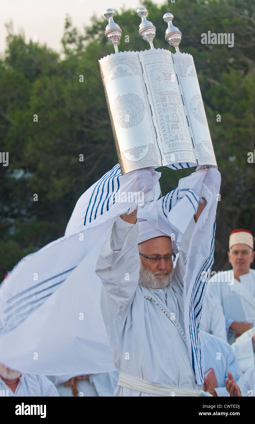 A priest of the ancient Samaritan community holds up a Torah scroll during the holy day of Shavuot in Mount Gerizim - Stock Image