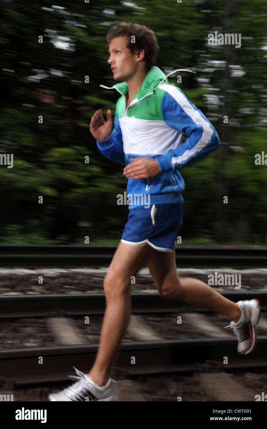 Young man running at railway tracks - Stock Image