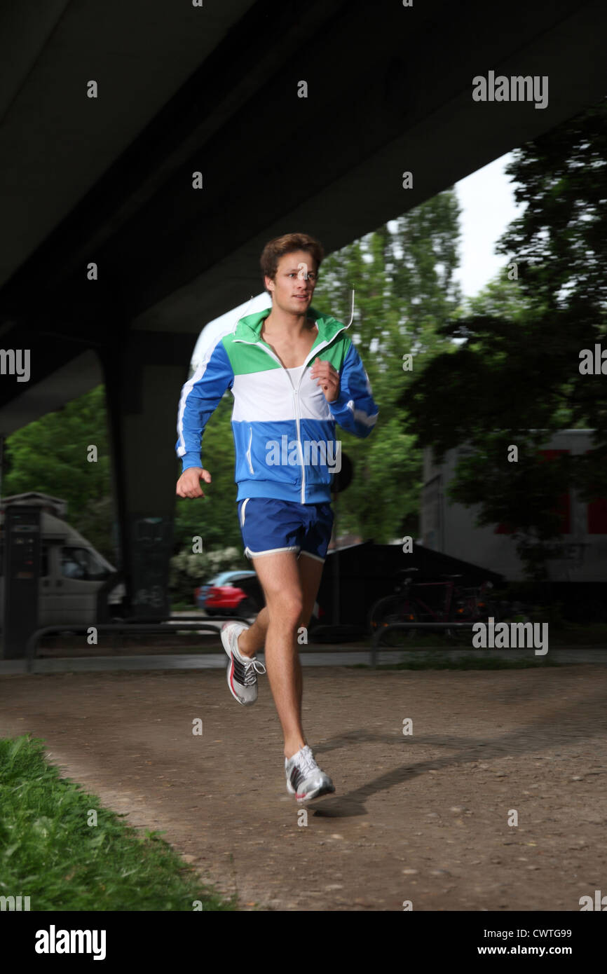 Young man running under bridge - Stock Image