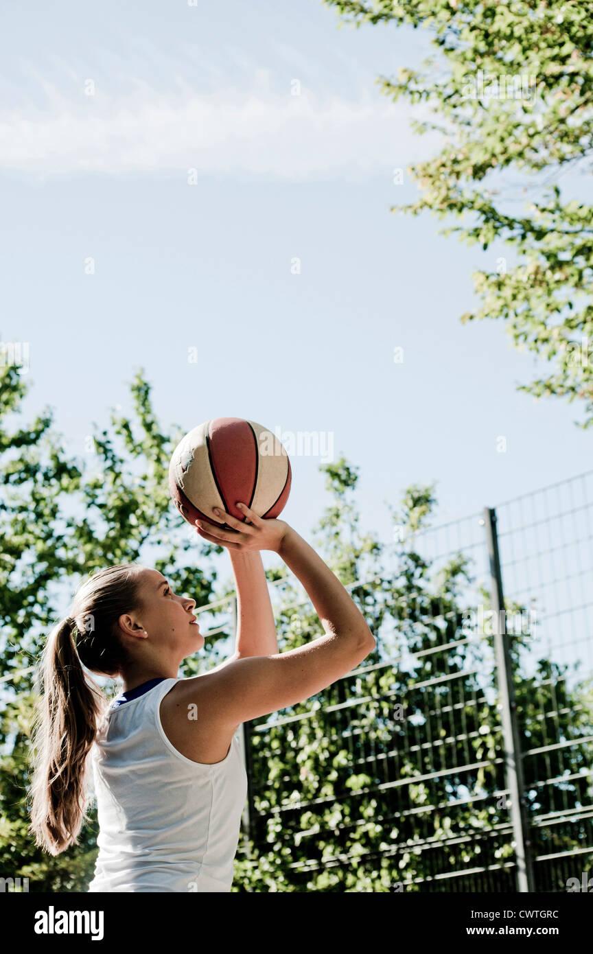 Teenage girl throwing basketball - Stock Image