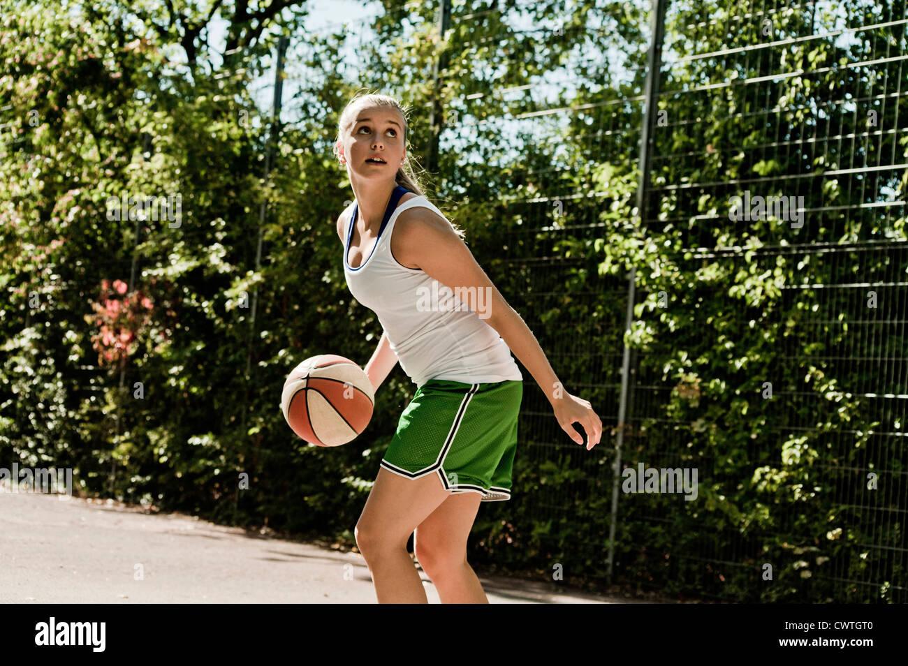 Teenage girl playing basketball - Stock Image