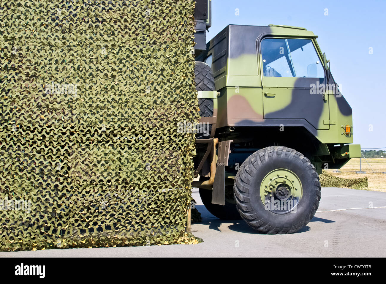 military vehicle hung with camouflage netting - Stock Image