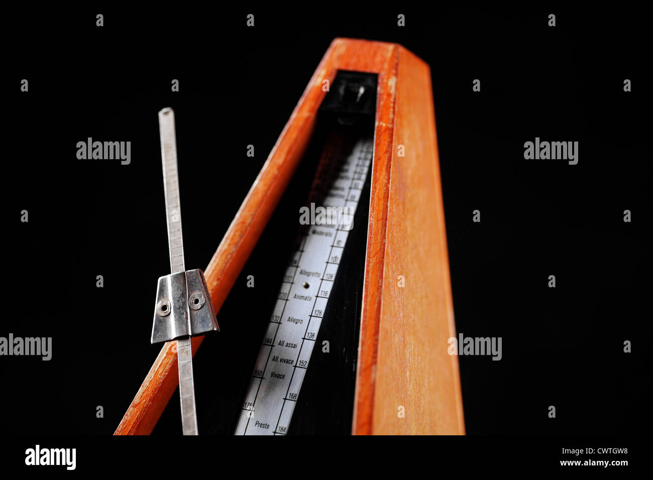 Vertical shot of a vintage metronome, on black - Stock Image