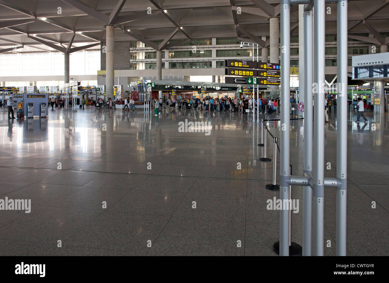 A busy airport terminal concourse with passenger queues in the background - Stock Image