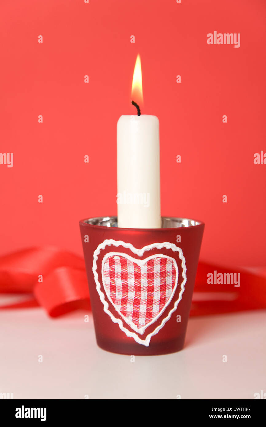 Burning candle with heart-shaped candle holders - Stock Image