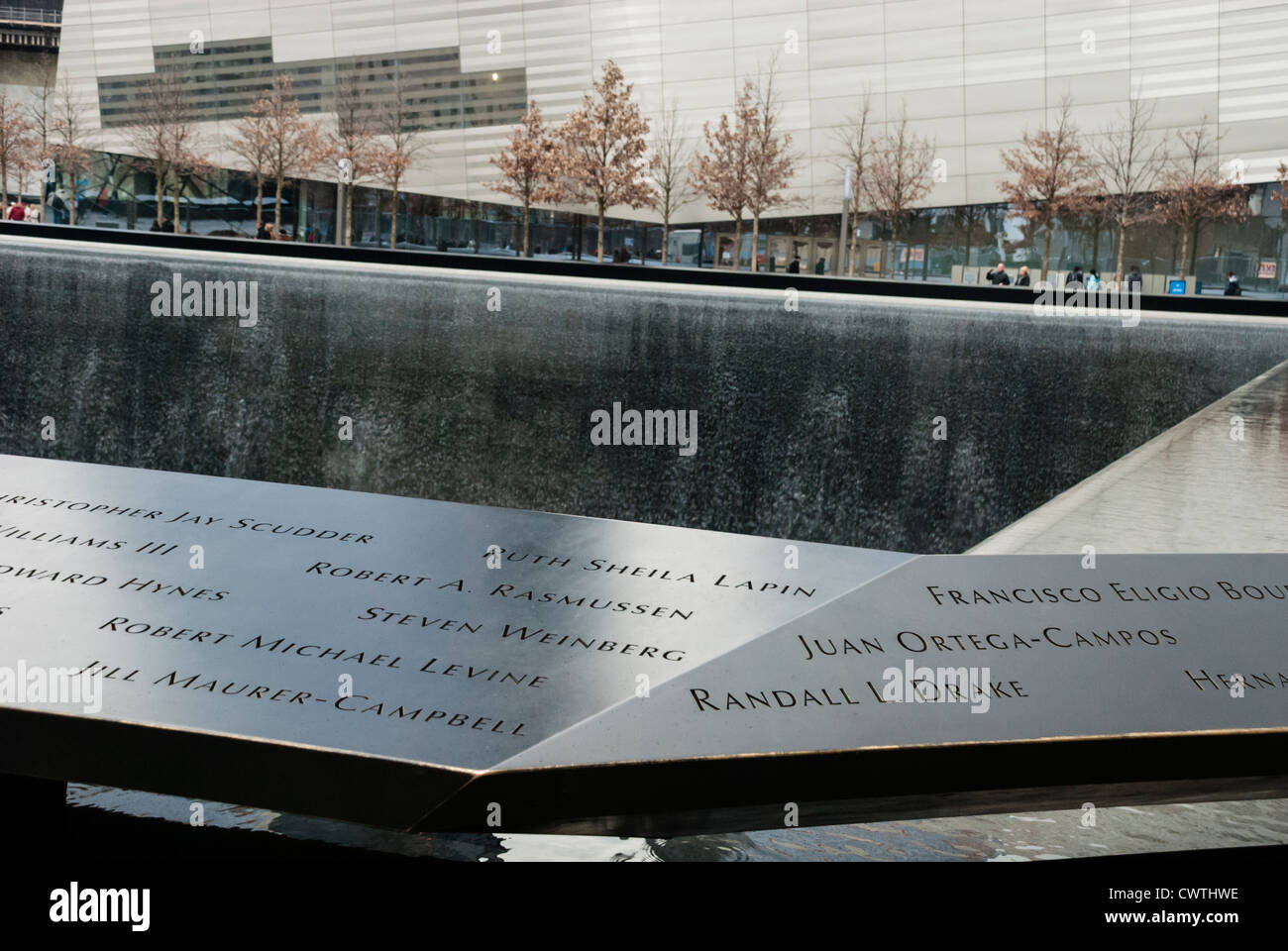 National September 11 Memorial showing names on the parapet surrounding the pool and the Museum in the background. - Stock Image
