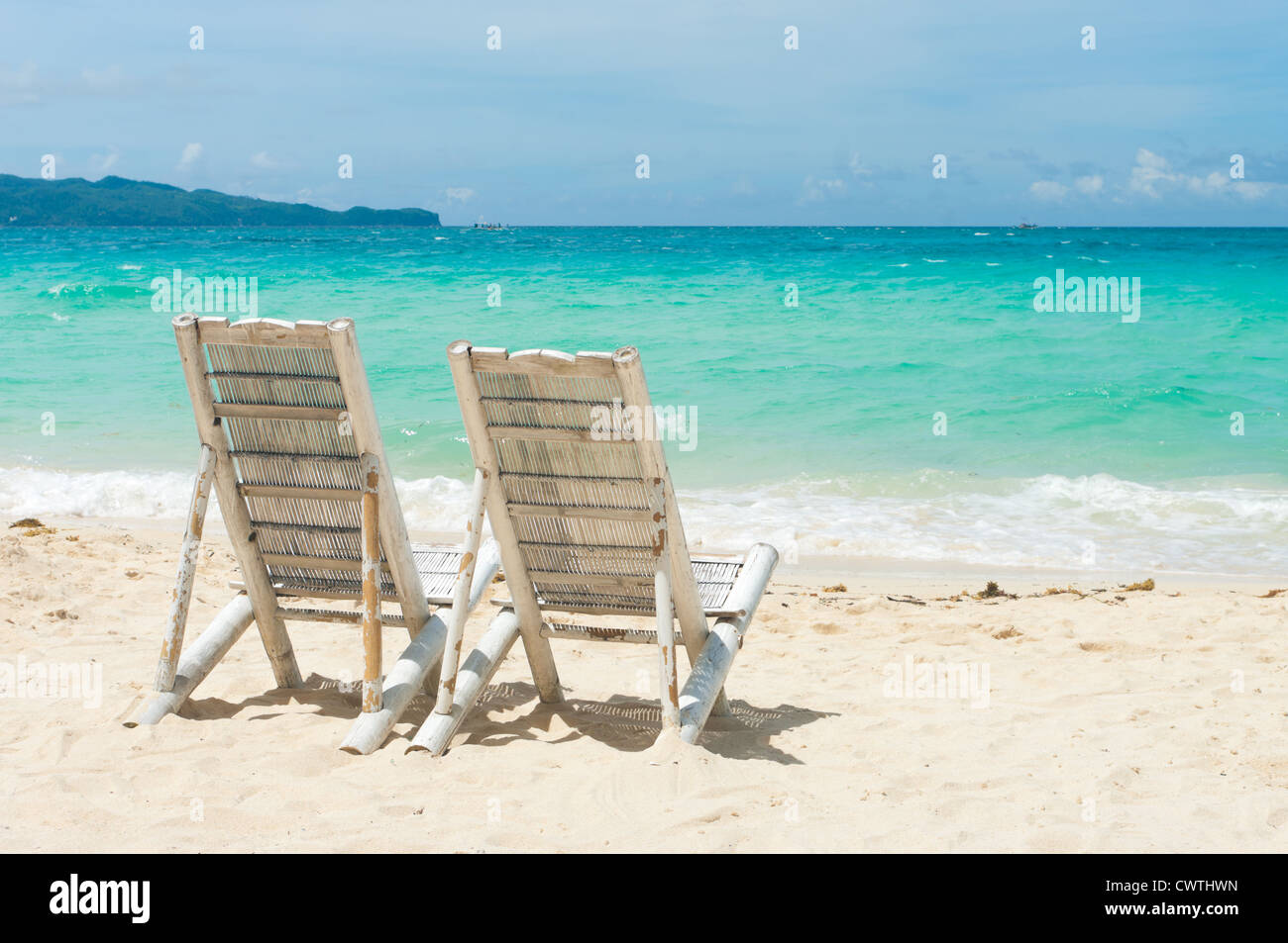 Tropical Beach With Two Beach Chairs Facing The Blue Sea