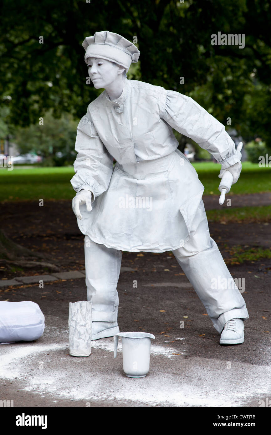 Street artist (mime) acting as a baker character - Stock Image