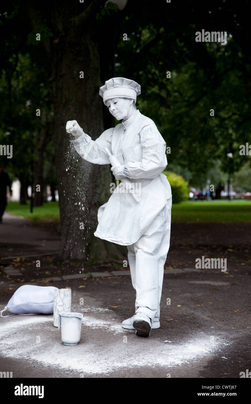 Street (baker) mime pouring flour to the ground - Stock Image