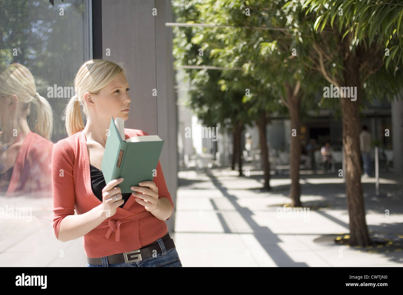 Young woman leaning against glass wall reading book - Stock Image