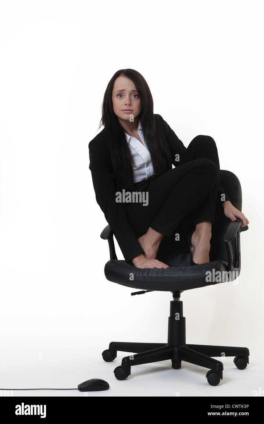 business woman who doesn't like mice crouched on an office chair looking down at a computer mouse on the floor - Stock Image