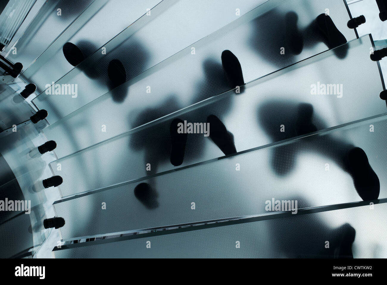 Feet walking on a glass staircase in the Apple NYC Fifth Avenue store. Feet are seen from underneath so silhouetted Stock Photo