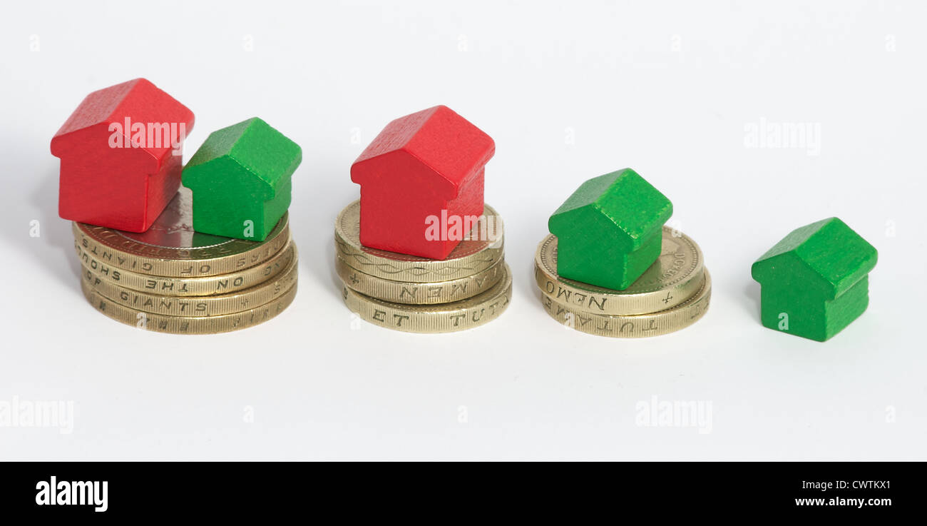 Monopoly houses stood on stacks of British one and two pound coins. SIgnifies that more money means more and bigger - Stock Image