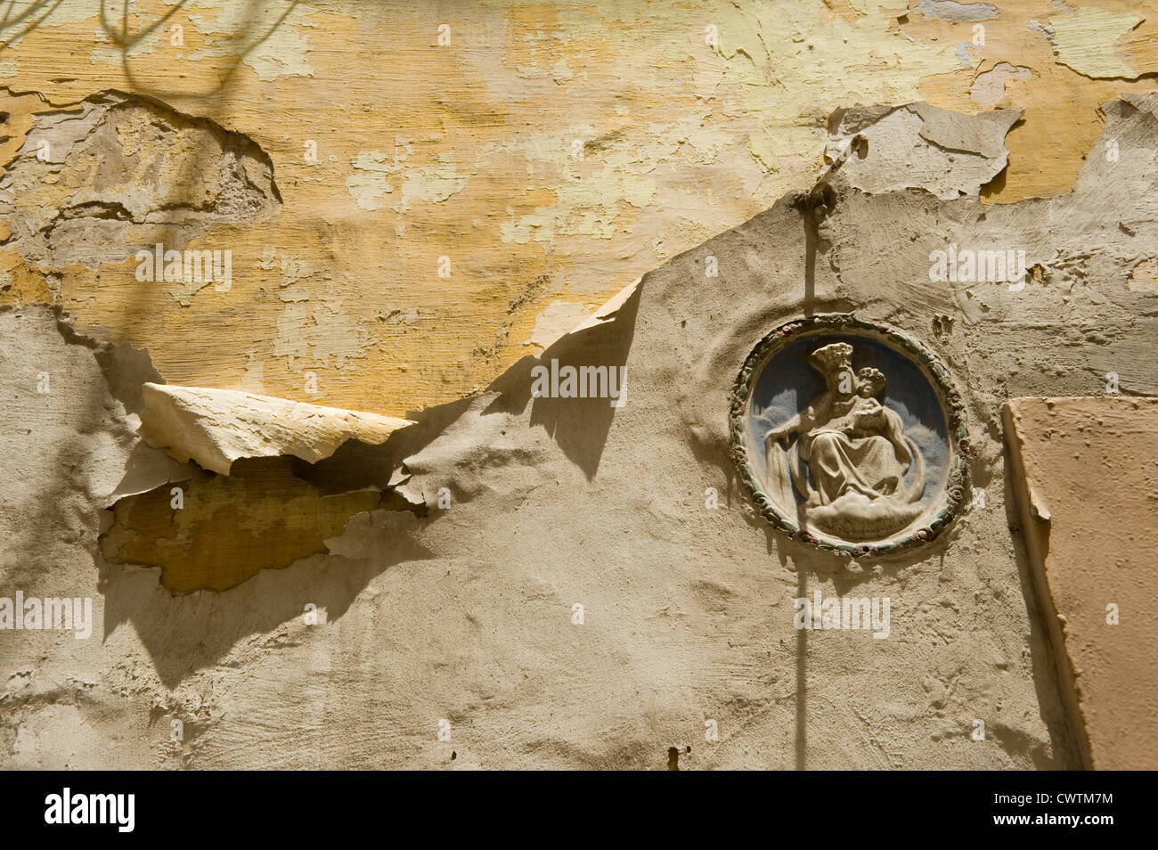 Flaking paint and small plaque in a backstreet of Valletta, capital city of Malta. - Stock Image
