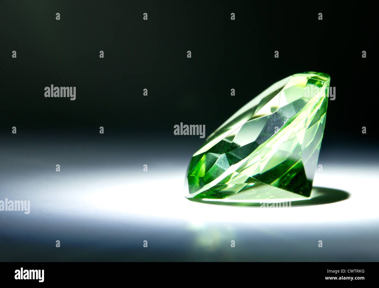 Faceted round cut green gemstone painted with light - Stock Image