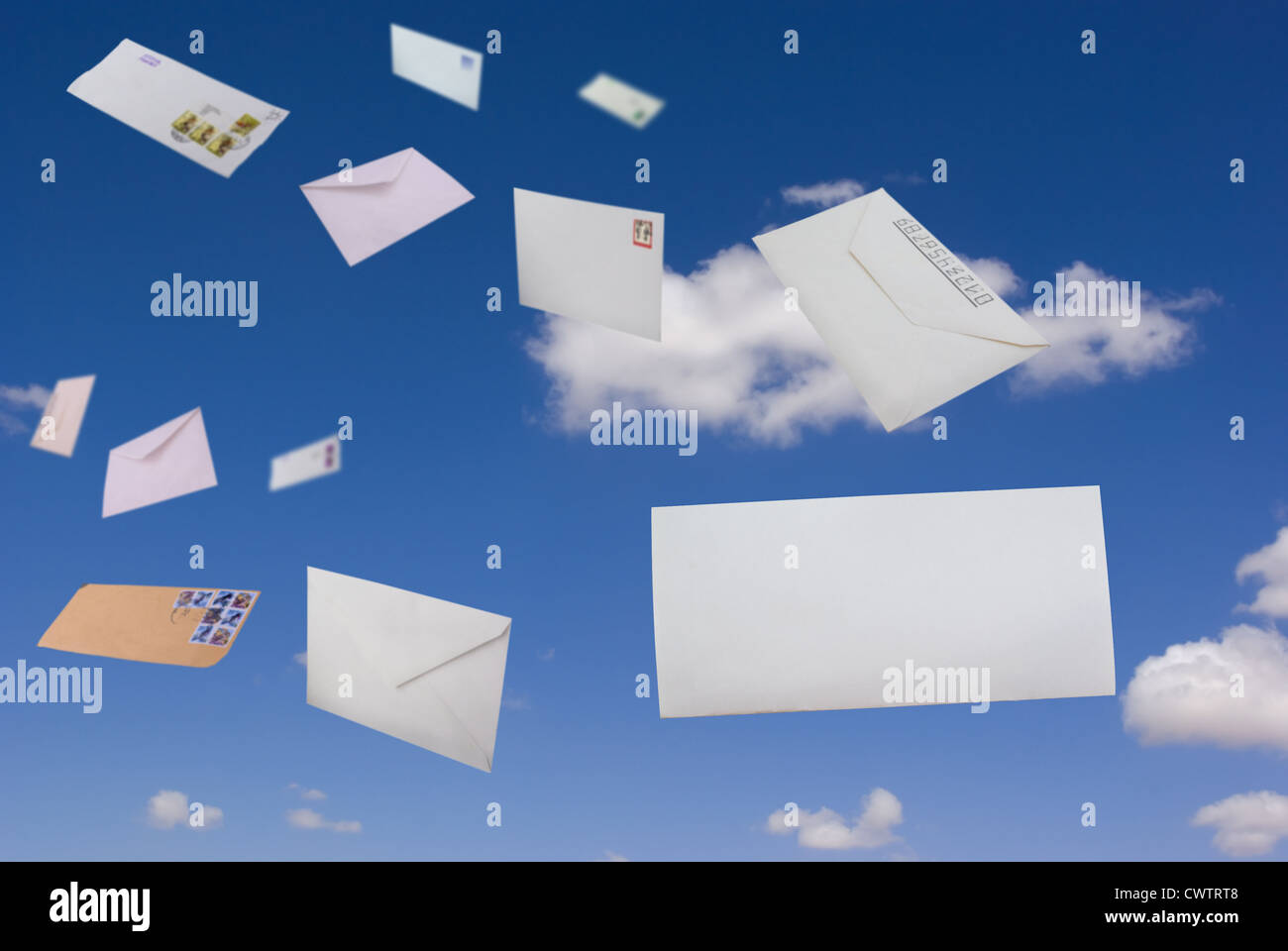 Envelopes flying against the blue sky and clouds - Stock Image