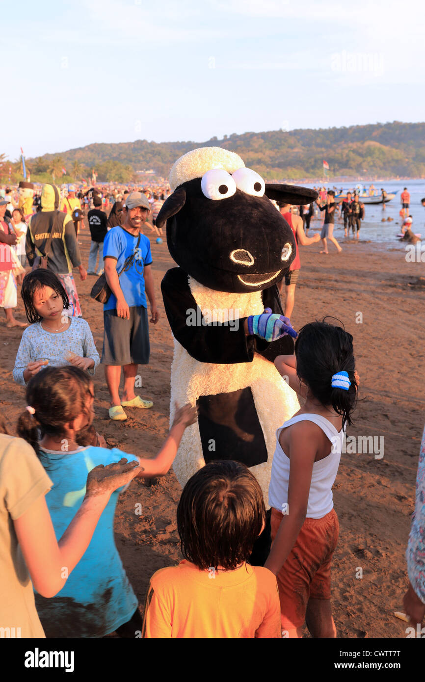 Person dressed as Shaun the sheep entertains children on the beach at Pangandaran, West Java - Stock Image