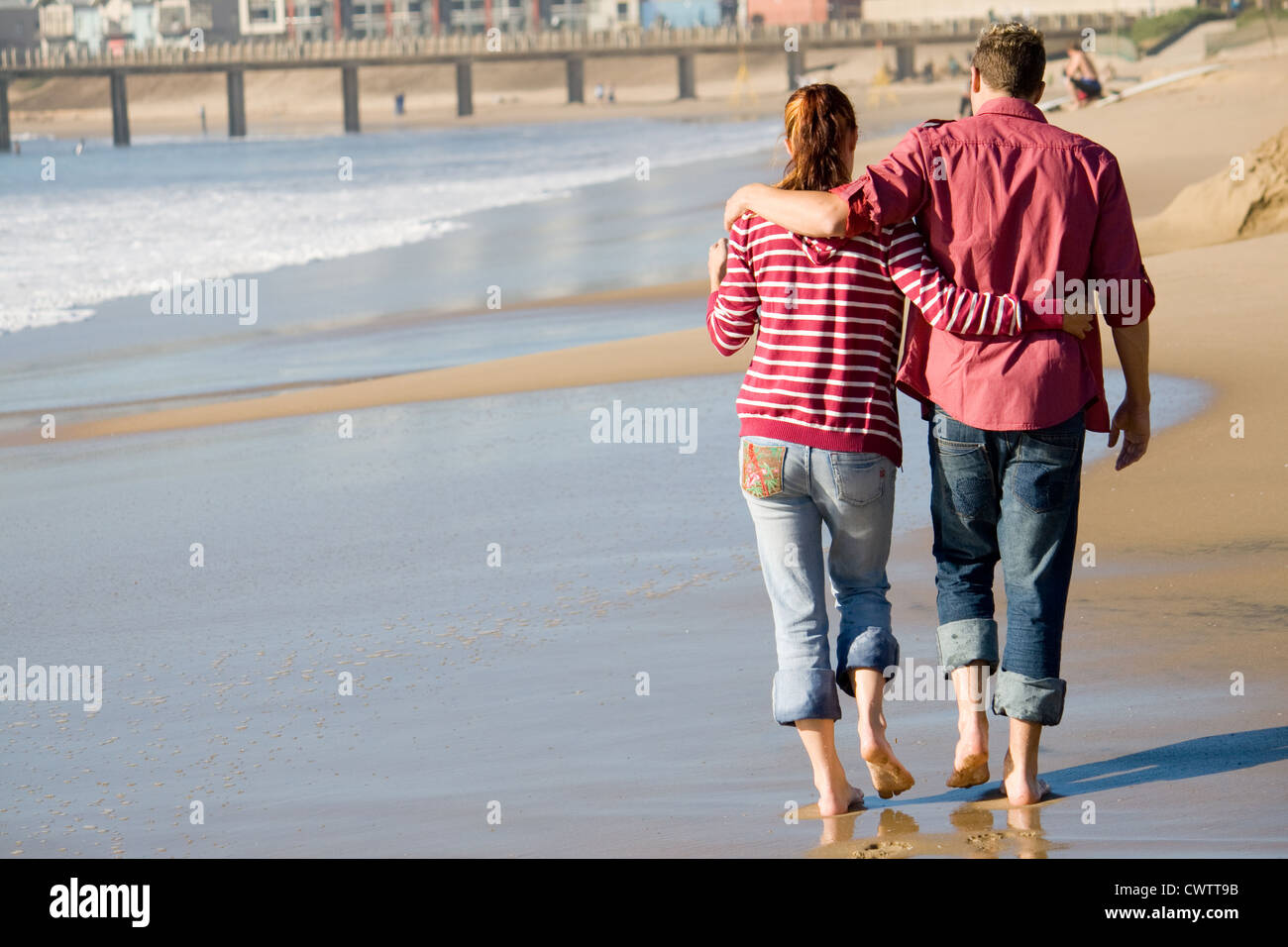 young couple walking on beach - Stock Image