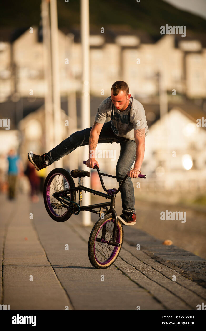 Summer evening: a young man doing a  foot jam endo stunt on a BMX bike, Aberystwyth Wales UK - Stock Image