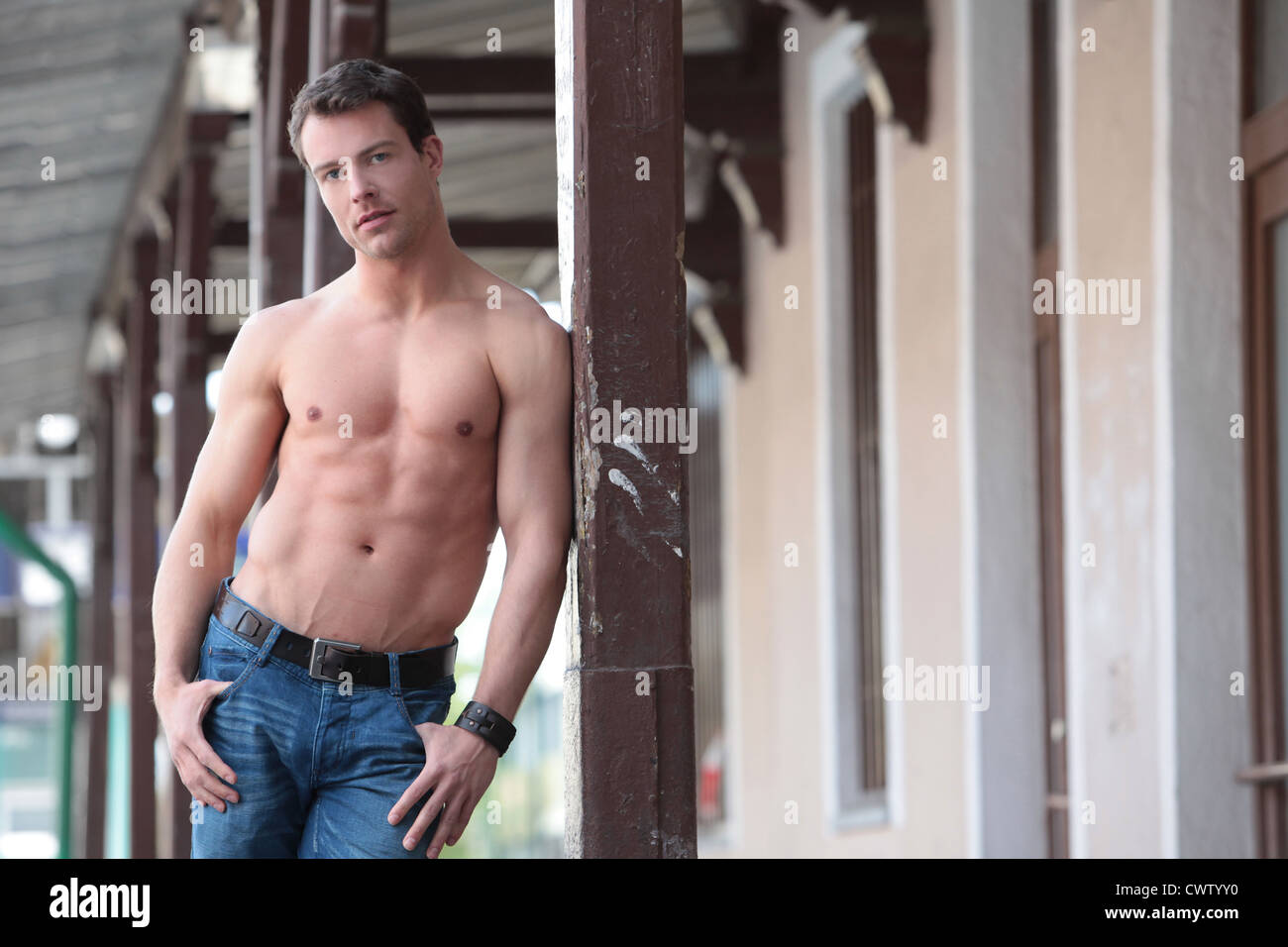 Barechested man standing outdoors - Stock Image