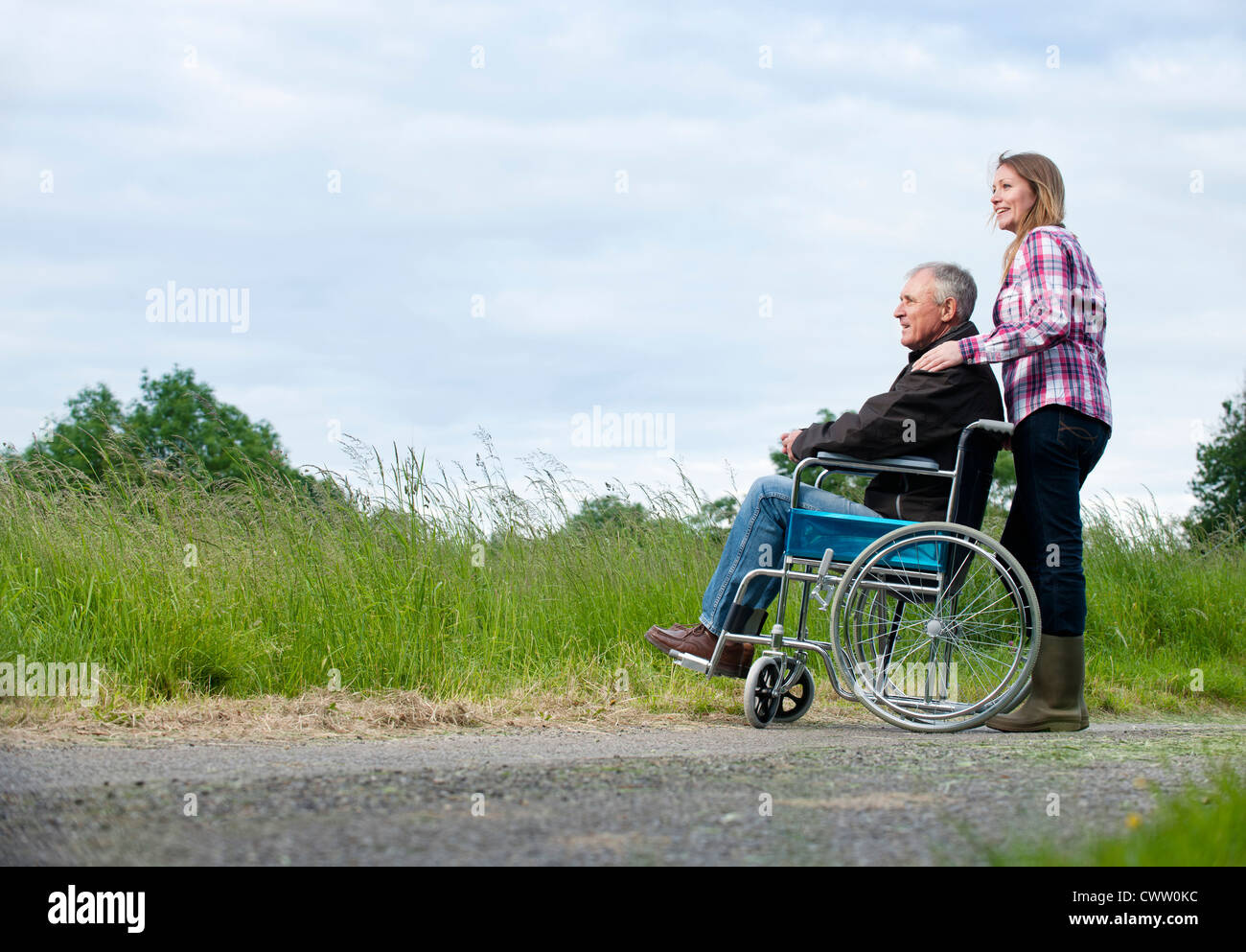 Woman pushing father in wheelchair - Stock Image
