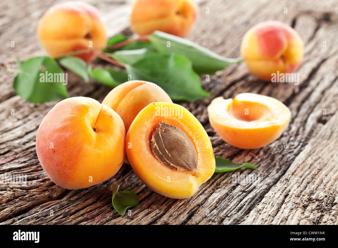 Apricots with leaves on the old wooden table. - Stock Image