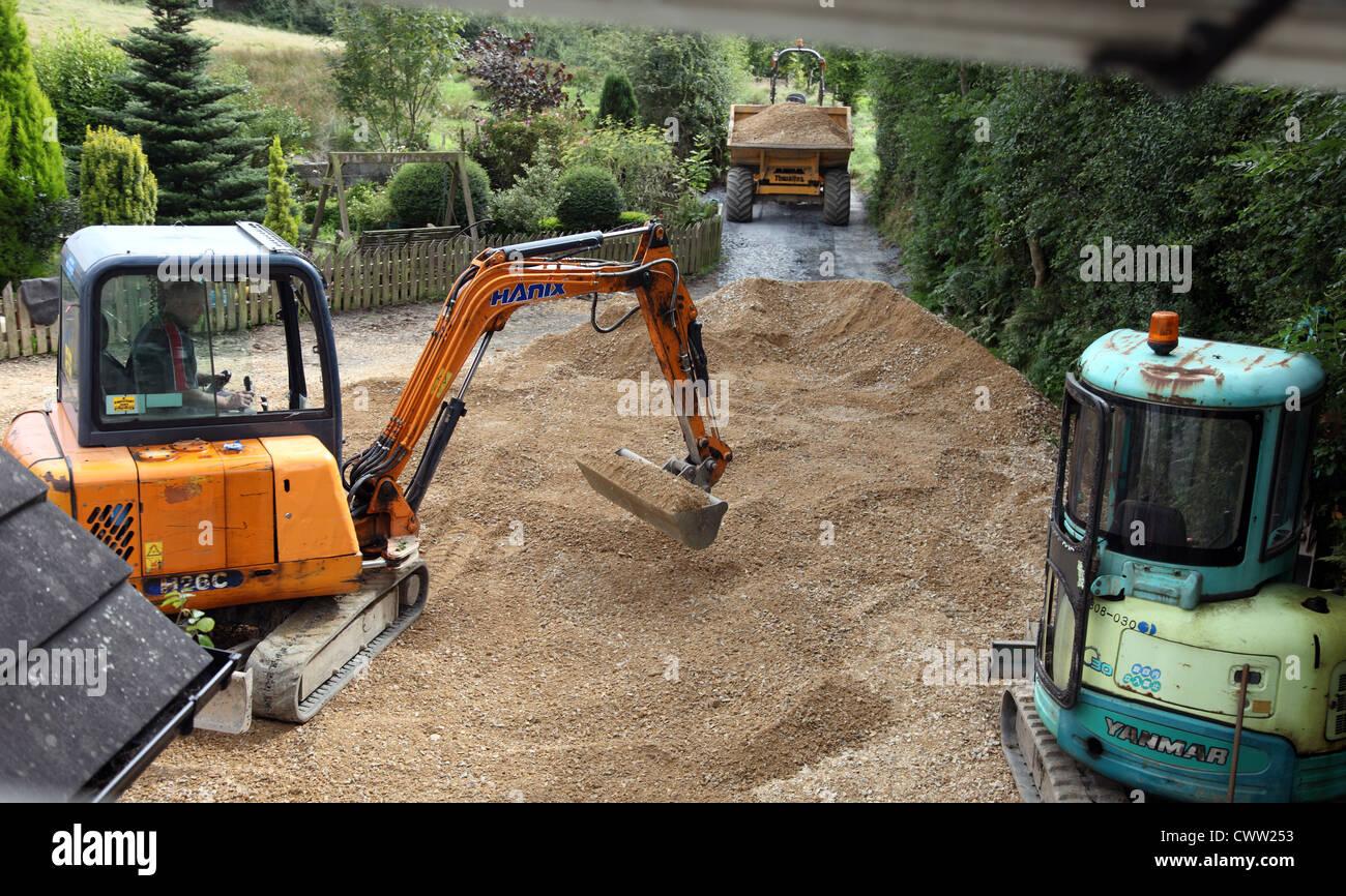 Spreading limestone gravel on an Irish farmyard - Stock Image