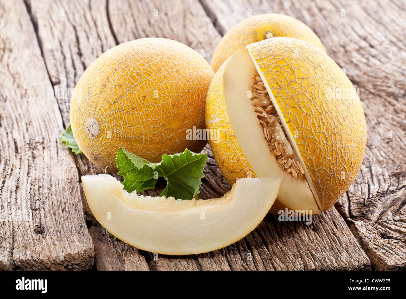 Melon With Slices And Leaves On A Old Wooden Table Stock Photo