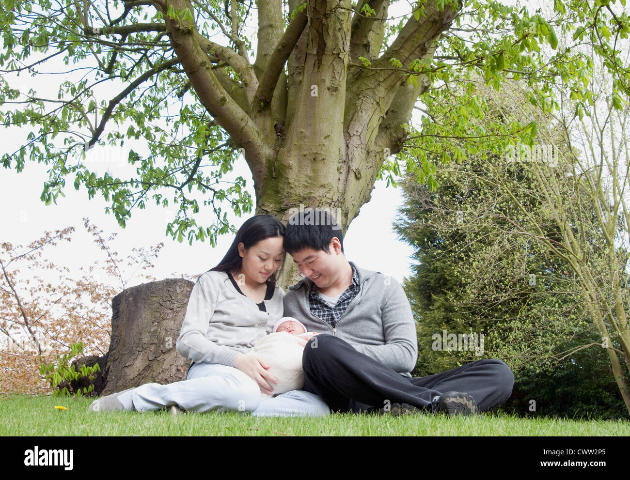 Parents holding sleeping baby in park - Stock Image