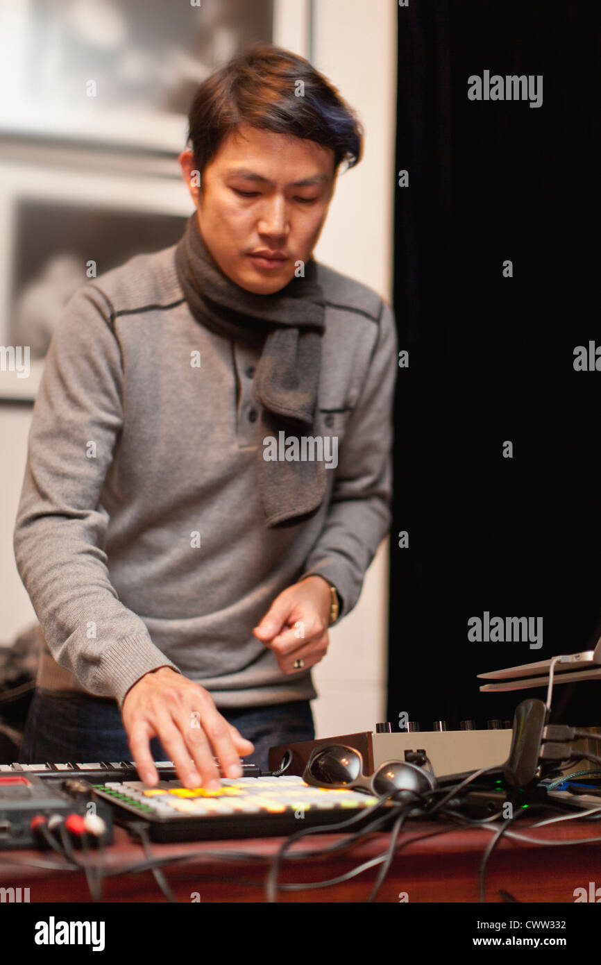 Musician playing with synthesizer - Stock Image