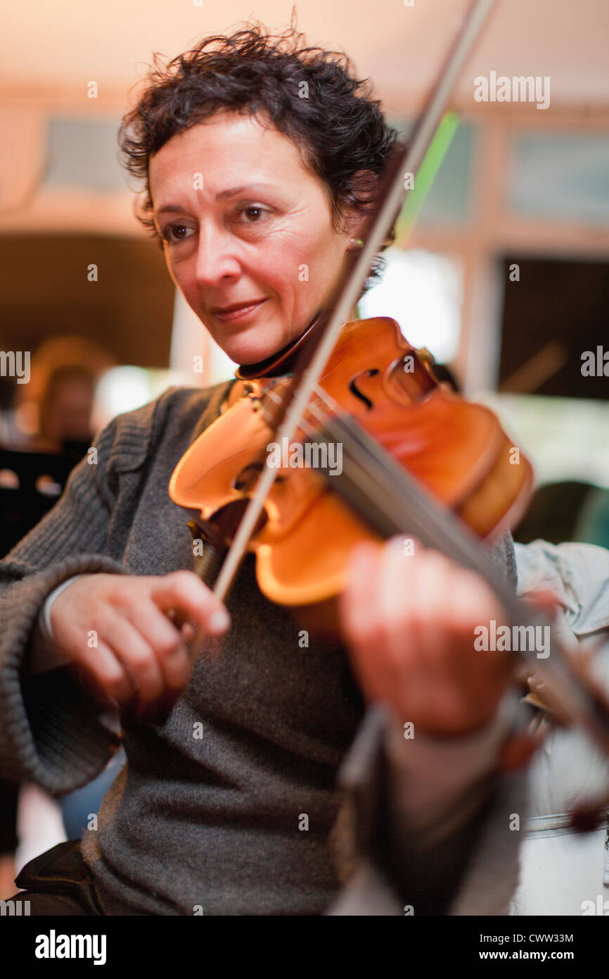 Violin player practicing with group - Stock Image