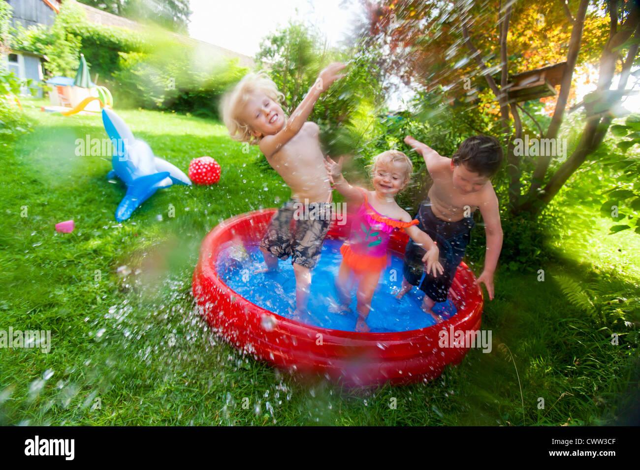 Children splashing in paddling pool - Stock Image