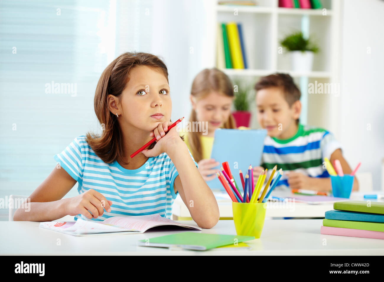 Portrait of lovely girl concentrating on drawing at workplace with schoolmates on background - Stock Image