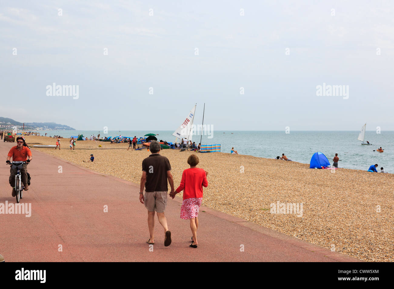 People walking on seafront promenade beside the sea and pebble beach on the south coast at Hythe, Kent, England, - Stock Image