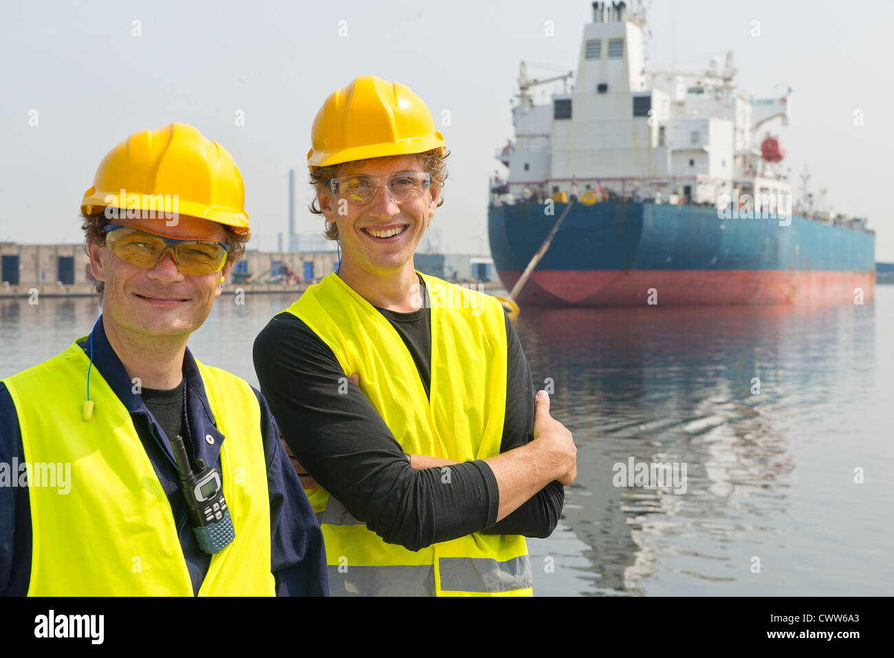 Happy, smiling dockers posing in front of a large industrial oil tanker - Stock Image