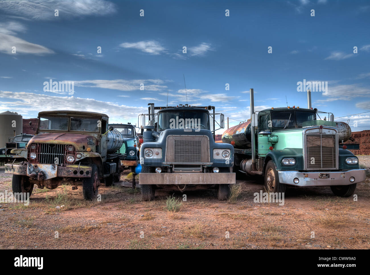 Junkyard with three trucks standing in the foreground - Stock Image