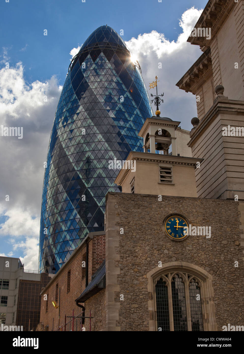The Gherkin building in the City of London contrasts with the older surrounding architecture - Stock Image