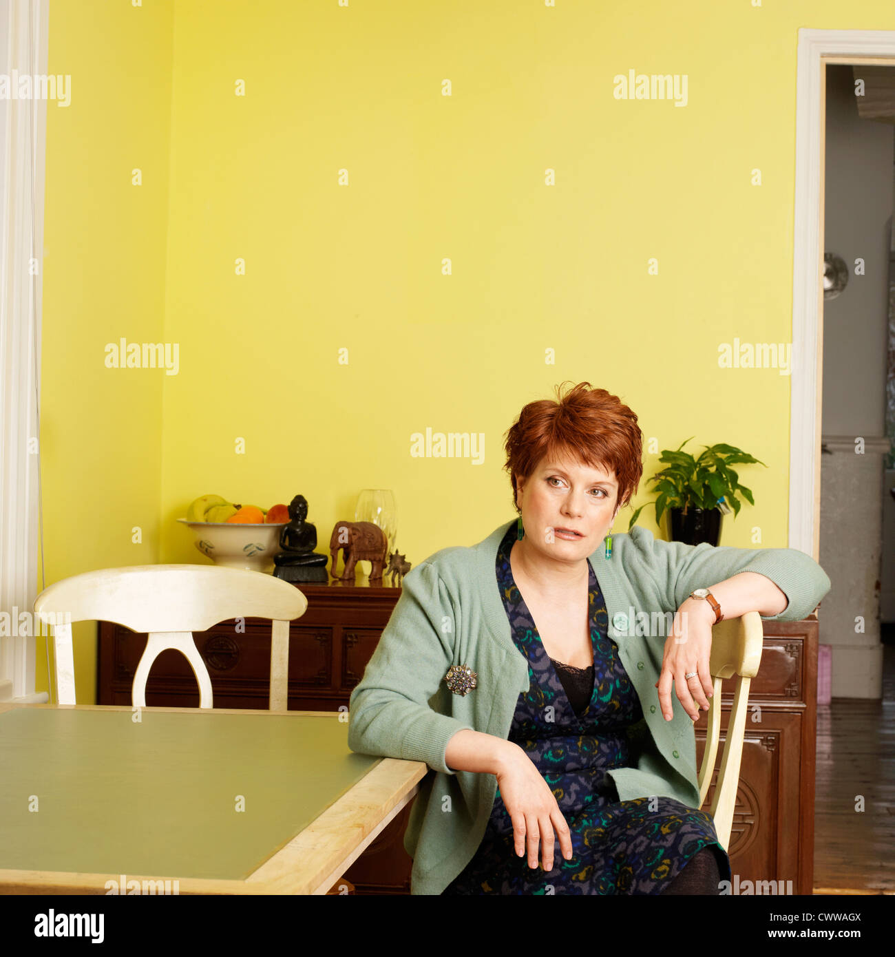 Woman sitting at kitchen table - Stock Image