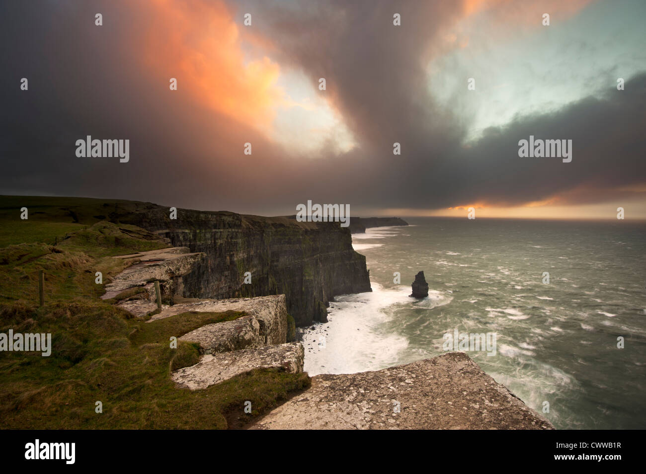 Colorful clouds over coastal cliffs - Stock Image