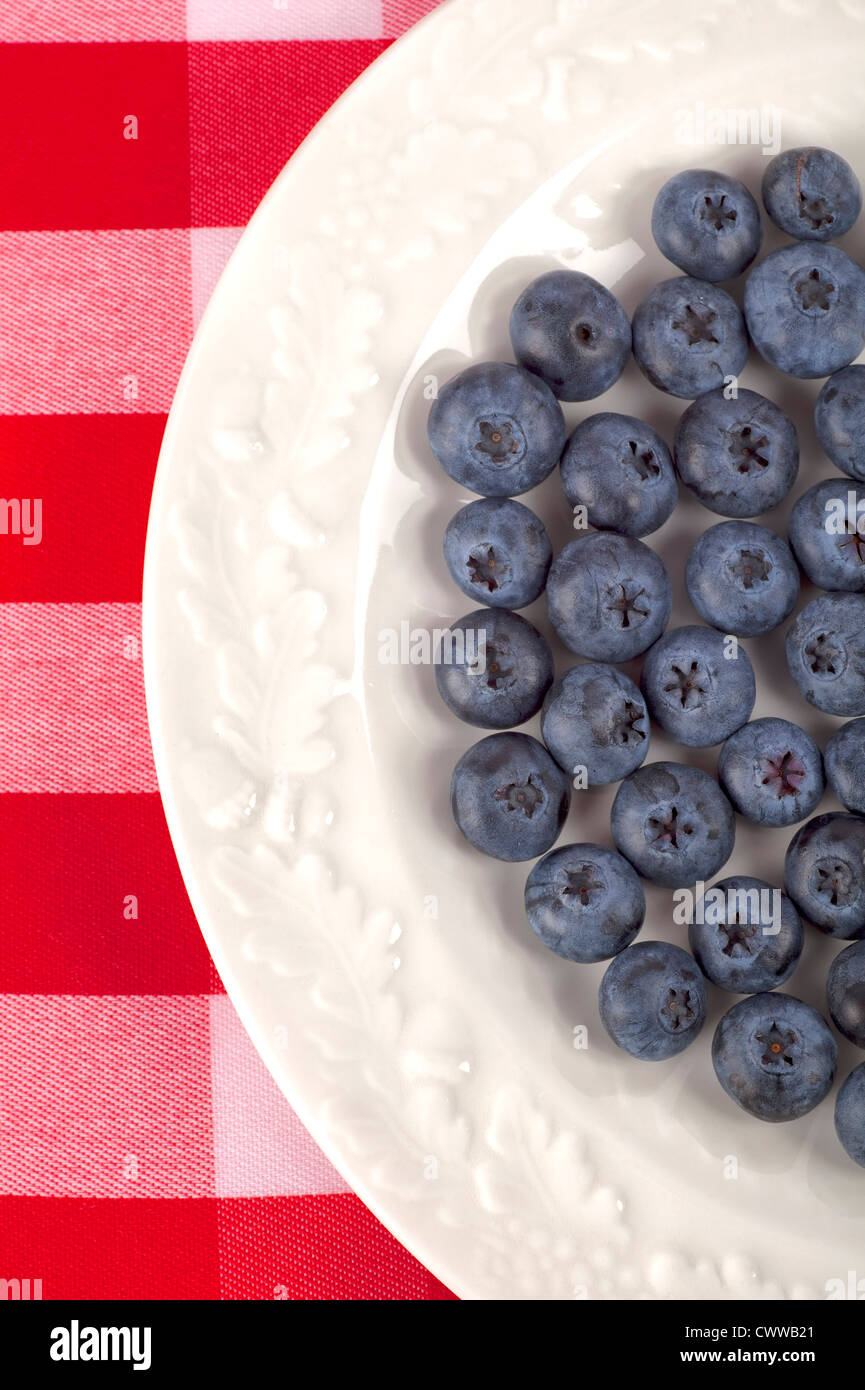 Highbush blueberries on a shiny glazed china plate on a gingham tablecloth. - Stock Image