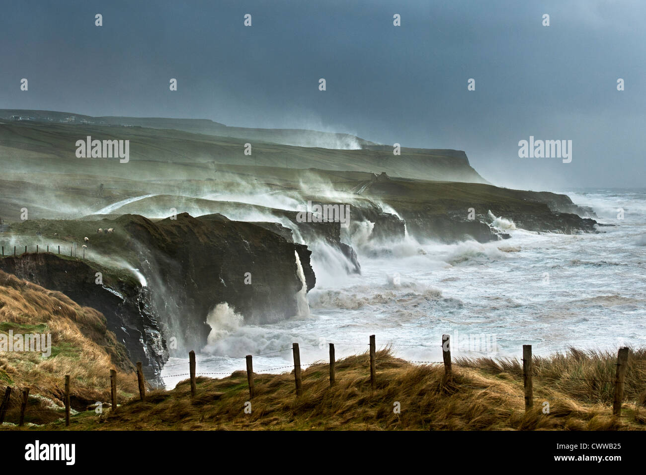 Waves crashing on rocky cliffs - Stock Image