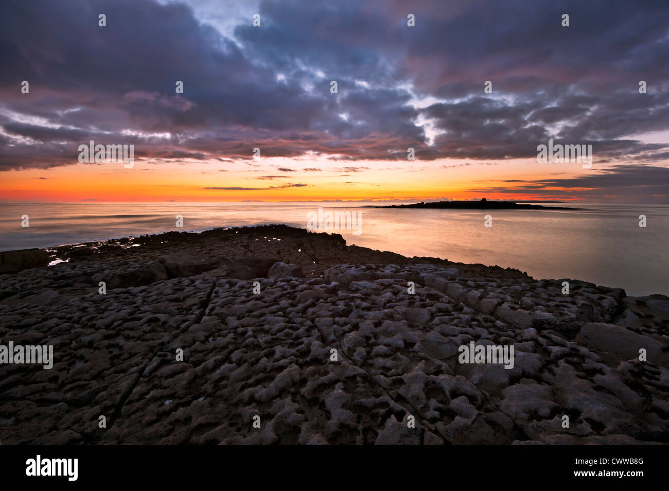 Sun setting over beach rock formations - Stock Image