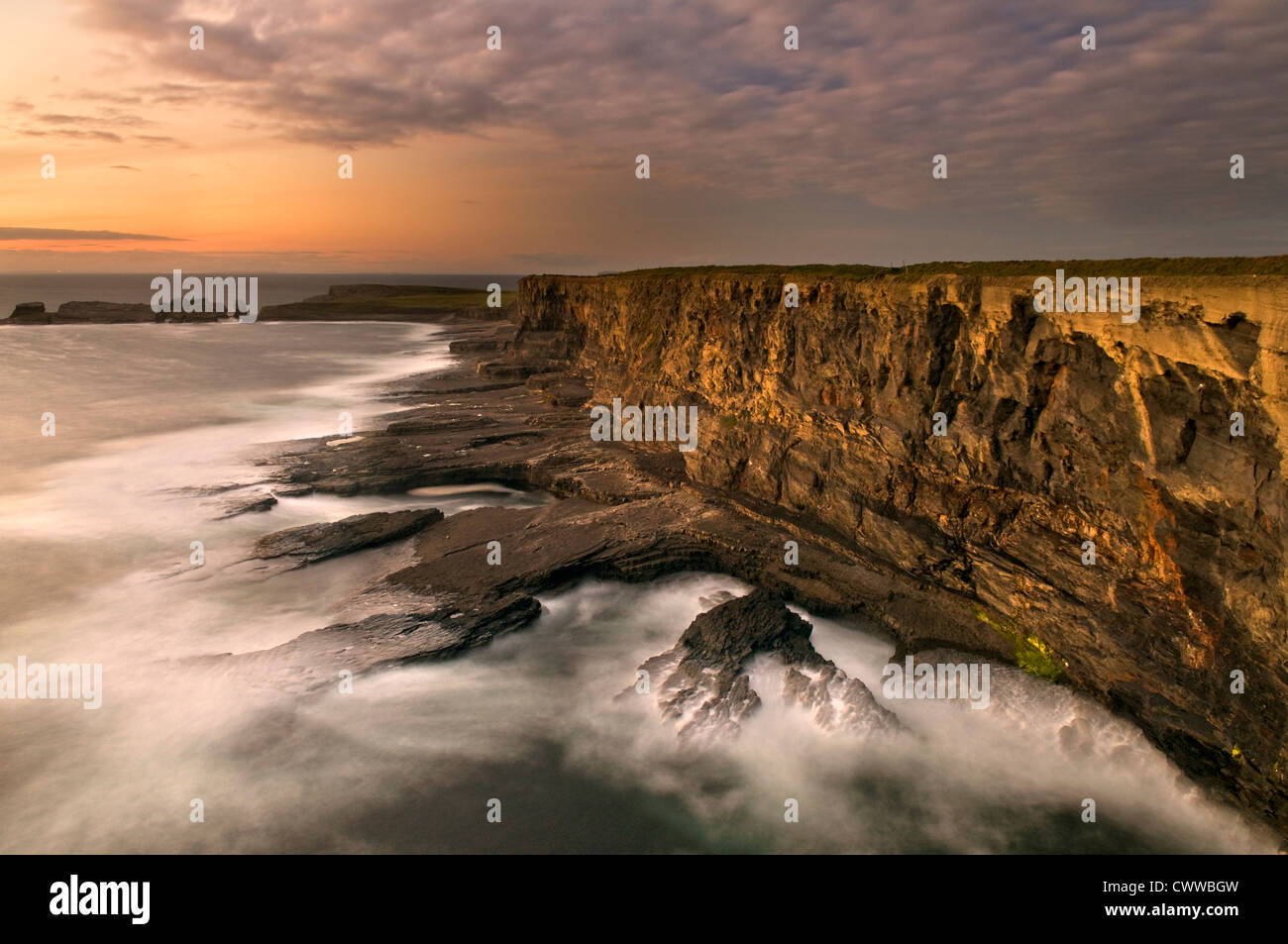 Fog rolling up to rocky coastal cliffs - Stock Image