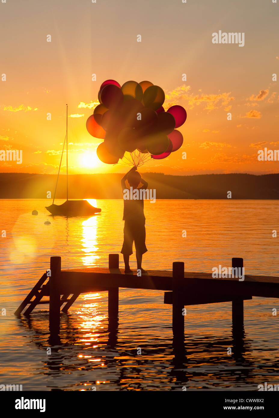 Boy holding balloons on wooden dock Stock Photo