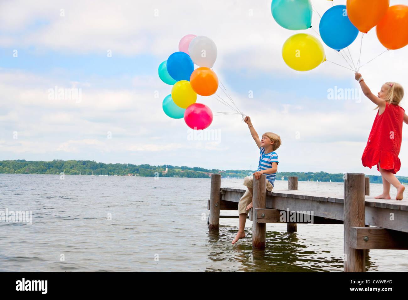 Children holding balloons on wooden pier - Stock Image