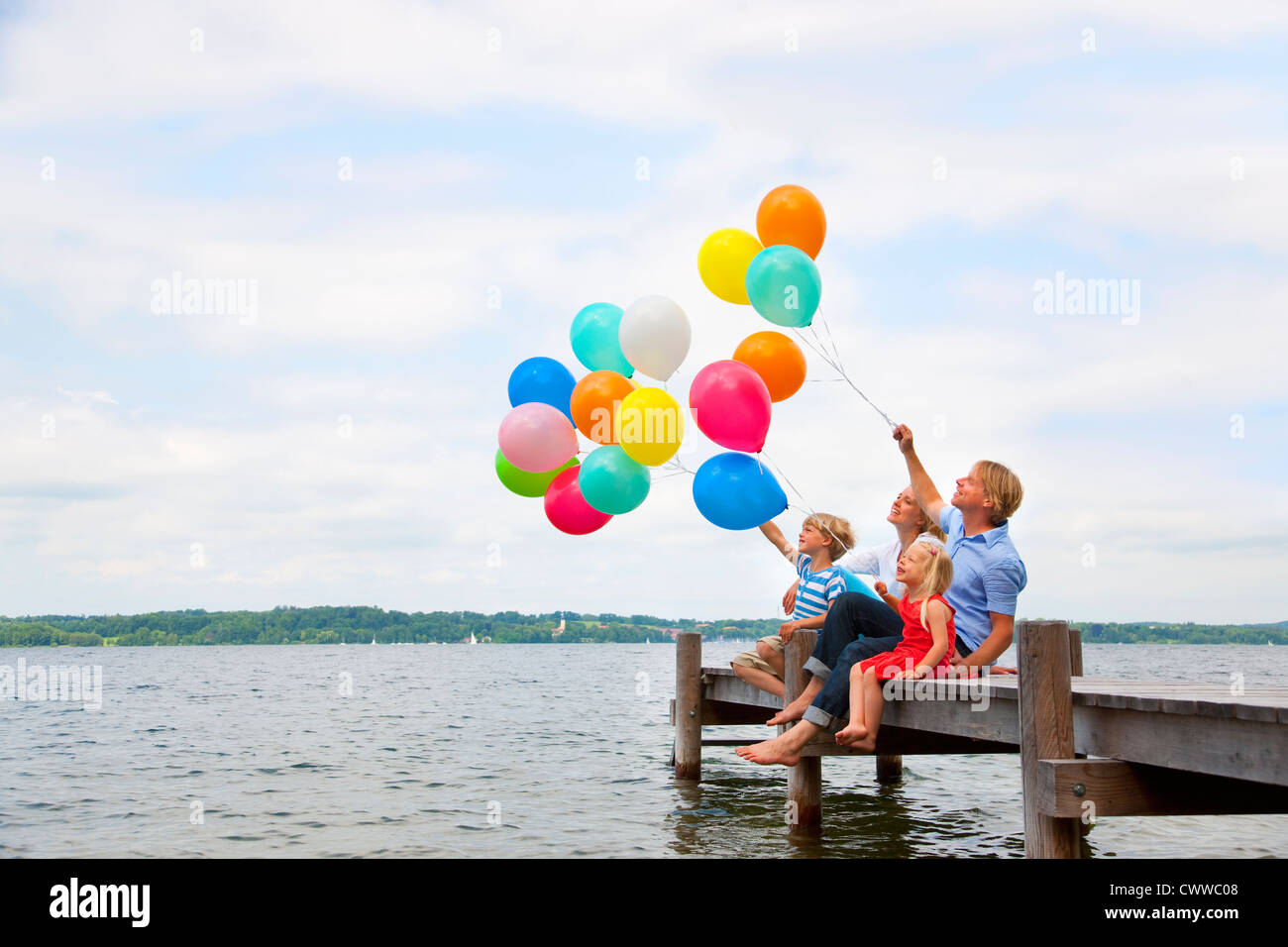 Family holding balloons on wooden pier - Stock Image